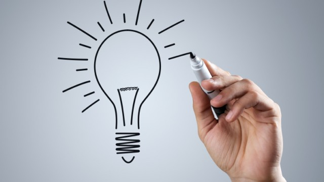 Male hand drawing light bulb over dark background