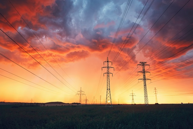 Dangerous weather Electricity pylons with power lines in stunning storm during colorful sunset.