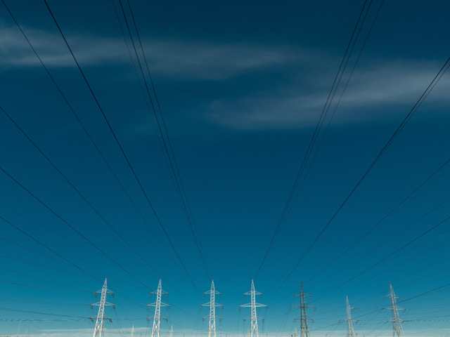 perspective view of electricity power lines on blue sky background